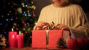 Fille heureuse redressant l'arc sur le grand boîte-cadeau, présents pendant des vacances, traditions photos stock