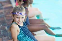 Fille heureuse s'asseyant avec des amis au poolside Images libres de droits
