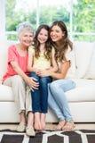 Fille heureuse s'asseyant avec la mère et la grand-mère sur le sofa Photo stock