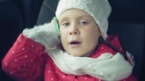 Fille heureuse s'asseyant dans le siège arrière d'une voiture et parlant au téléphone banque de vidéos