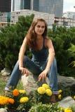 Fille heureuse s'asseyant parmi des fleurs dans le jardin Photo stock
