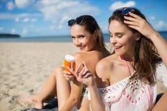 Fille heureuse s'asseyant sur la plage donnant l'huile de bronzage à son ami Image libre de droits