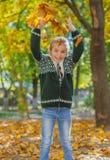 Fille heureuse sautant avec les feuilles jaunes image libre de droits