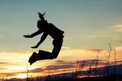 Fille heureuse sautant sur la côte du lac de au temps de coucher du soleil Photographie stock libre de droits