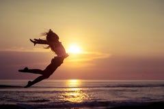 Fille heureuse sautant sur la plage au temps de coucher du soleil Images libres de droits
