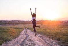 Fille heureuse sautant sur la route au coucher du soleil photos libres de droits