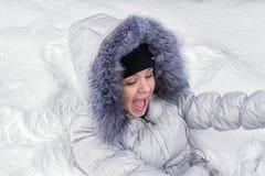 Fille heureuse se situant dans la neige Photographie stock libre de droits