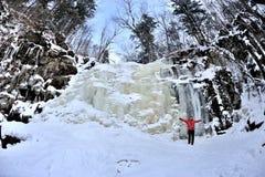 Fille heureuse se tenant au-dessus de la cascade congelée Photo libre de droits