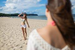 Fille heureuse se tenant sur la plage souriant à son ami Photos stock