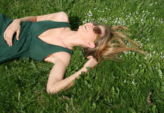 Fille heureuse se trouvant sur l'herbe Photographie stock libre de droits