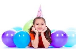 Fille heureuse se trouvant sur le plancher avec les ballons colorés Image stock