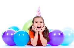Fille heureuse se trouvant sur le plancher avec les ballons colorés Photographie stock