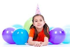 Fille heureuse se trouvant sur le plancher avec les ballons colorés Photographie stock libre de droits
