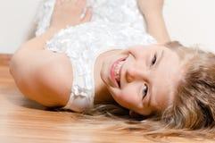 Fille heureuse se trouvant sur le plancher souriant et regardant dans l'appareil-photo image stock