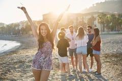 Fille heureuse soulevant des mains sur la plage se tenant avec des amis Image libre de droits