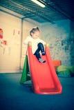 Fille heureuse sur la glissière colorée Photographie stock libre de droits
