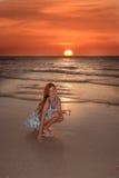Fille heureuse sur la plage au coucher du soleil Photographie stock