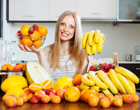 Fille heureuse tenant de divers fruits dans la cuisine à la maison Photographie stock libre de droits