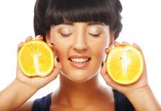 Fille heureuse tenant des oranges au-dessus de visage Photos stock