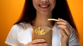 Fille heureuse tenant des pommes frites, des saveurs artificielles et la dépendance augmentée de goût photos stock