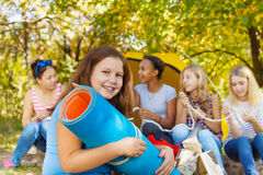 Fille heureuse tenant le tapis de spandex roulé par bleu Images libres de droits