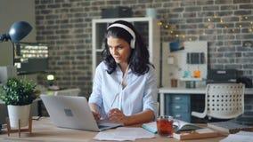 Fille heureuse travaillant avec l'ordinateur portable dactylographiant et écoutant la musique par des écouteurs banque de vidéos