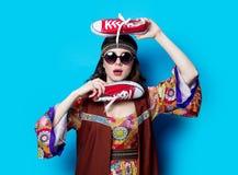 Fille hippie avec des lunettes de soleil et des chaussures en caoutchouc Images stock