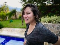 Fille hispanique appréciant des vacances dans la piscine avec un visage souriant et des cheveux humides photo stock