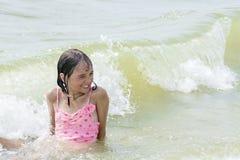 Fille humide heureuse sur la plage dans l'eau, sur un fond de grandes belles vagues, Photographie stock libre de droits