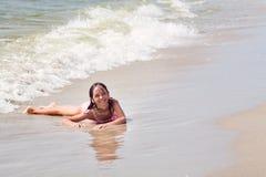 Fille humide heureuse sur la plage dans l'eau, sur un fond de grandes belles vagues Photographie stock
