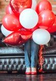 Fille inconnue cachée dans des ballons rouges et blancs d'hélium sur le sofa Ballons et jambes colorés de femmes dans des chaussu photos libres de droits