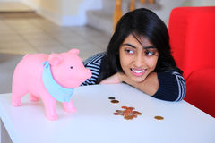 Fille indienne regardant à son Piggybank Images stock