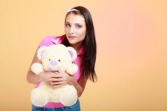 Fille infantile de femme puérile étreignant l'ours de nounours image stock