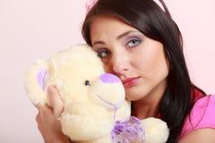 Fille infantile de jeune femme puérile dans le jouet étreignant rose d'ours de nounours photos stock