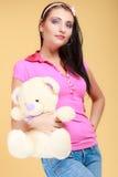 Fille infantile de jeune femme puérile dans le jouet étreignant rose d'ours de nounours photo libre de droits