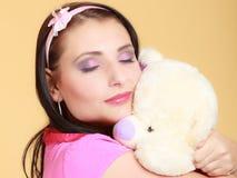 Fille infantile de jeune femme puérile dans le jouet étreignant rose d'ours de nounours photo stock
