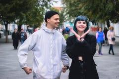 Fille informelle avec des cheveux bleus et un homme avec la peau pâle à la marche de rue Image libre de droits