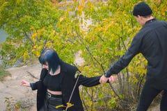 Fille informelle avec des cheveux bleus et un homme avec la peau pâle dans des vêtements noirs à la marche de rue Photo stock