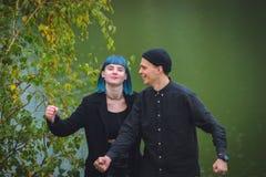 Fille informelle avec des cheveux bleus et un homme avec la peau pâle dans des vêtements noirs à la marche de rue Photos stock