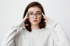 Fille inquiétée émotive avec les lunettes de port de cheveux foncés tenant des mains sur la tête, se sentant embarrassé et frustr image libre de droits