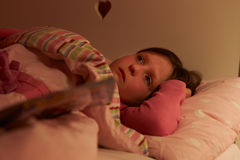 Fille inquiétée se situant dans le lit éveillé la nuit photographie stock libre de droits
