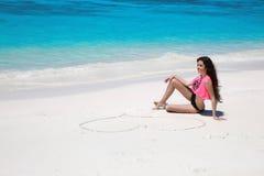 Fille insouciante de modèle de bikini avec le coeur sur le sable détendant sur exotique photographie stock