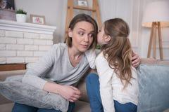 Fille inspirée disant des secrets à sa maman Image libre de droits