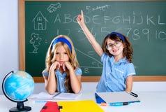 Fille intelligente d'étudiant de ballot dans la salle de classe soulevant la main Photographie stock