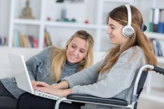 Fille invalide sur le fauteuil roulant avec l'ordinateur portable avec l'ami Photos stock