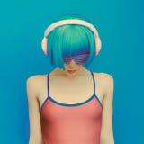 Fille irréelle du DJ dans des écouteurs à la mode écoutant la musique Photographie stock libre de droits