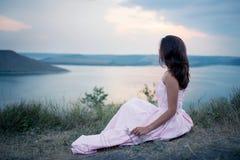 Fille isitting sur la banque de la rivière et observant le coucher du soleil photo stock