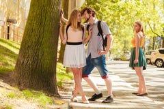 Fille jalouse regardant les couples de flirt extérieurs photographie stock libre de droits