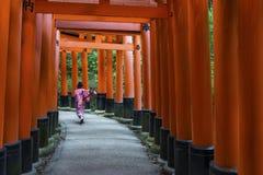 Fille japonaise courant par des portes de Torii chez Fushimi Inari-Taish Photographie stock libre de droits