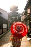 Fille japonaise dans Yukata avec le parapluie rouge dans la vieille ville Kyoto Photos stock